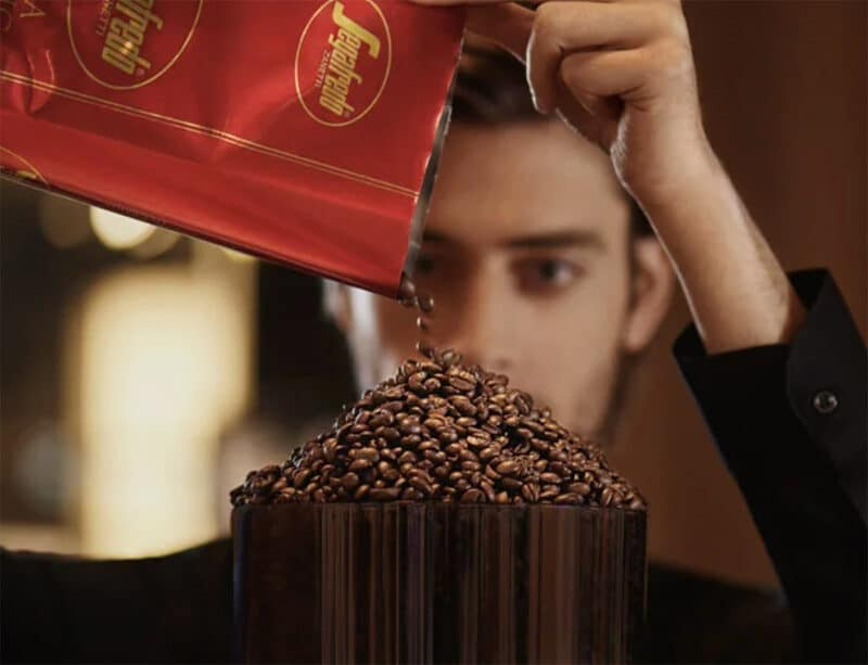 pouring extra strong coffee beans into grinder hopper